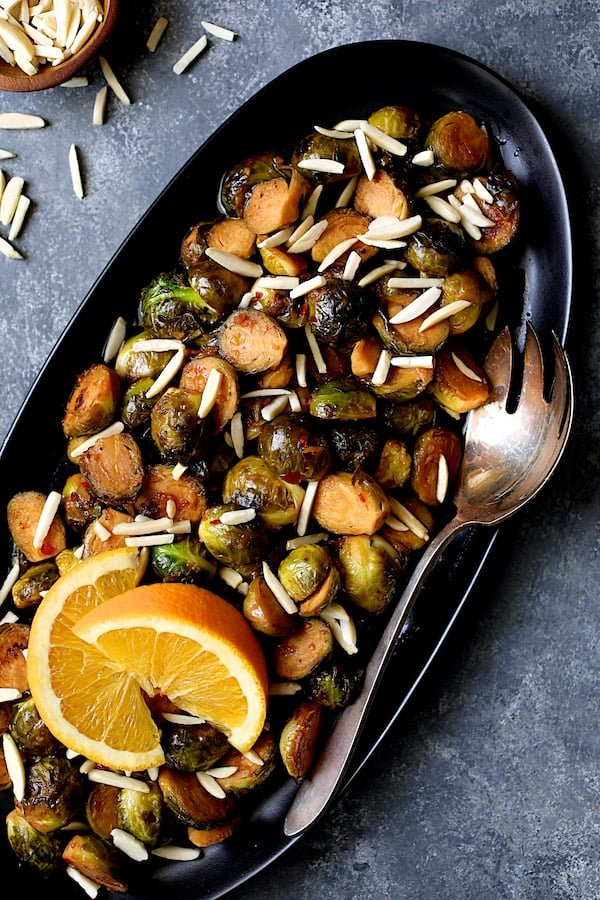 Pan-Roasted Brussels Sprouts with Thai Sweet Chili Orange Glaze - Shot of platter of sprouts on an angle garnished with two orange wedges
