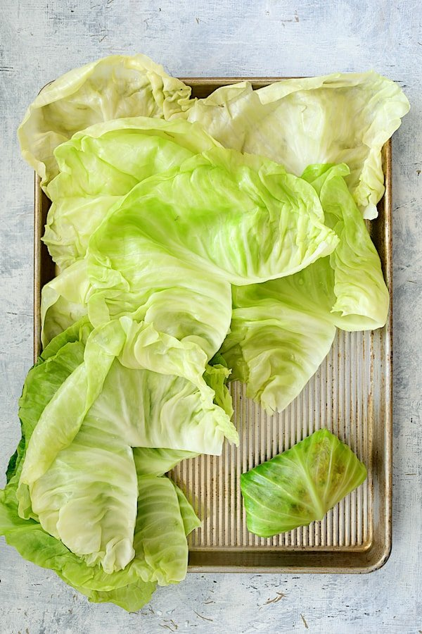 Spicy Italian Stuffed Cabbage - Overhead shot of cabbage leaves on baking sheet with one fully rolled