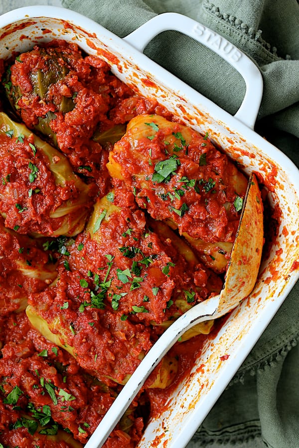 Spicy Italian Stuffed Cabbage - Close-up angled shot of baked cabbage rolls in white baking dish