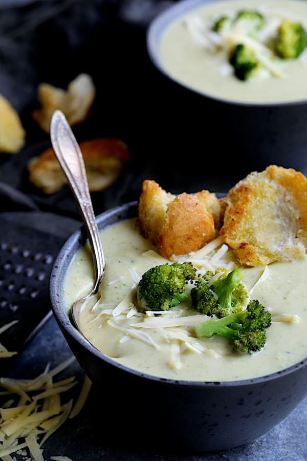 Broccoli Gruyere Soup with Torn Garlic Croutons - Straight-on close-up shot of soup garnished with broccoli, cheese and croutons