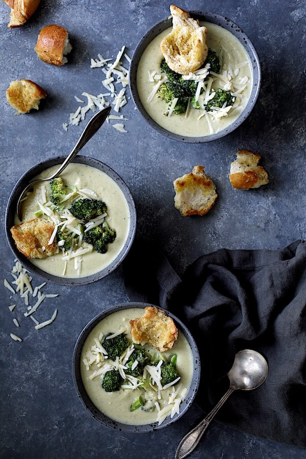 Broccoli Gruyere Soup with Torn Garlic Croutons - Overhead shot of three bowls of the soup garnished with cheese, broccoli and croutons