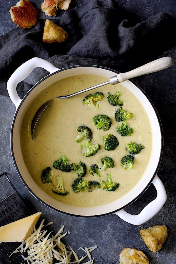 Broccoli Gruyere Soup with Torn Garlic Croutons - Overhead shot of soup in white Dutch oven on dark blue background