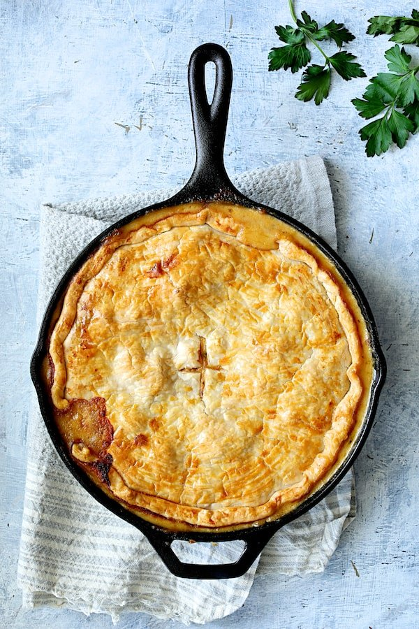 Photo of baked Cheesy Skillet Chicken Pot Pie on blue towel.