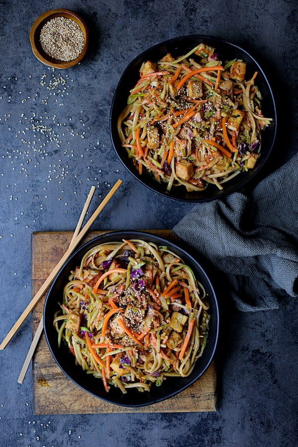 Thai Sesame Noodles with Tofu and Vegetables - Overhead shot of noodles in black bowls on dark blue background with chopsticks and gray napkin