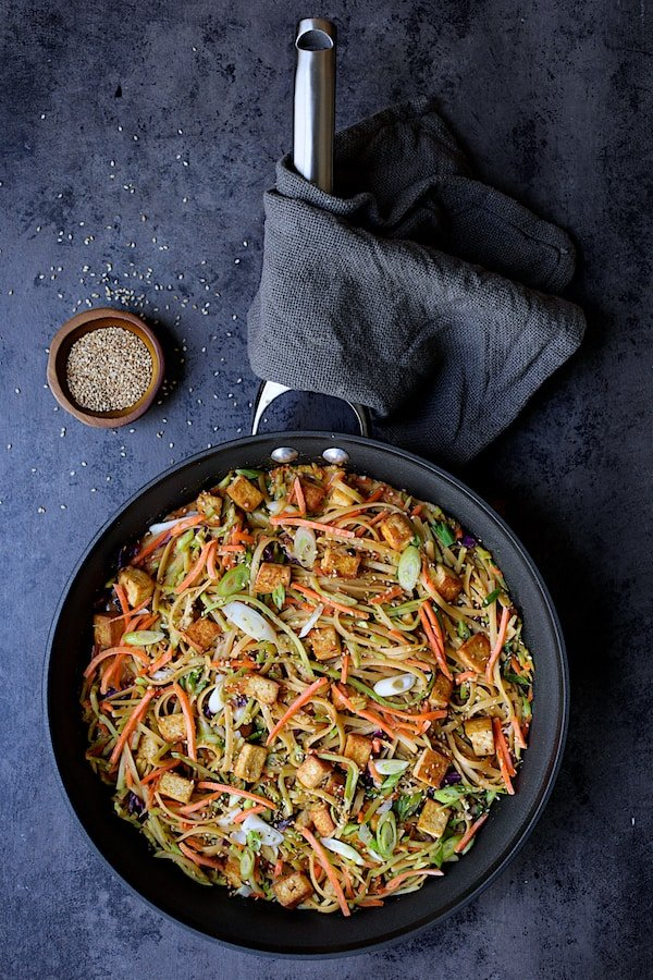 Thai Sesame Noodles with Tofu and Vegetables - Overhead shot of noodles in skillet garnished with sesame seeds