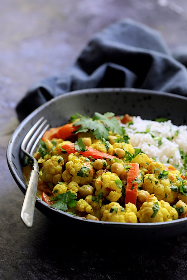 Vegan Indian Cauliflower and Chickpea Curry - Straight-on shot of a serving of the curry in gray bowl with basmati rice with gray napkin in the background