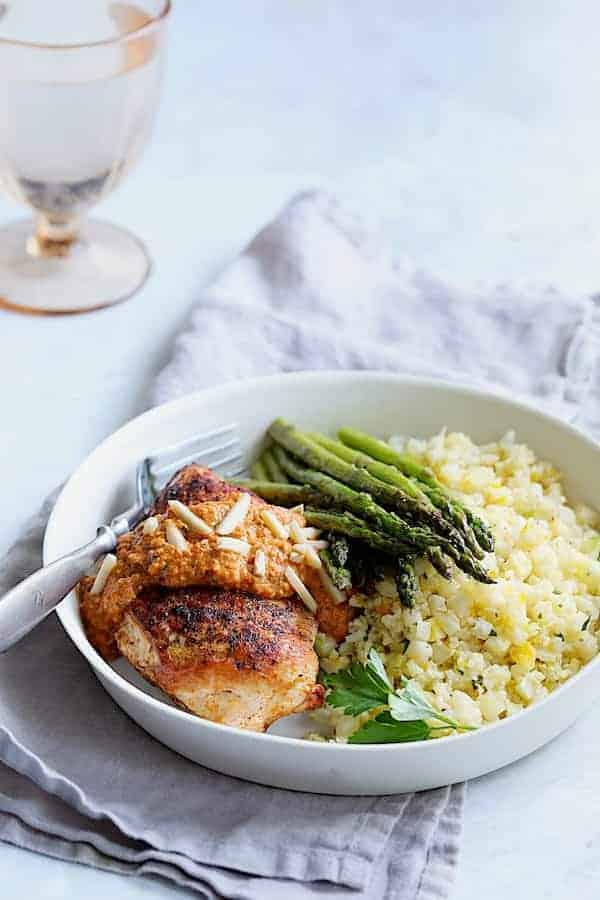 Chicken with Romesco Sauce and Saffron Cauliflower Rice - Straight-on shot of dish served in white bowl on gray napkin