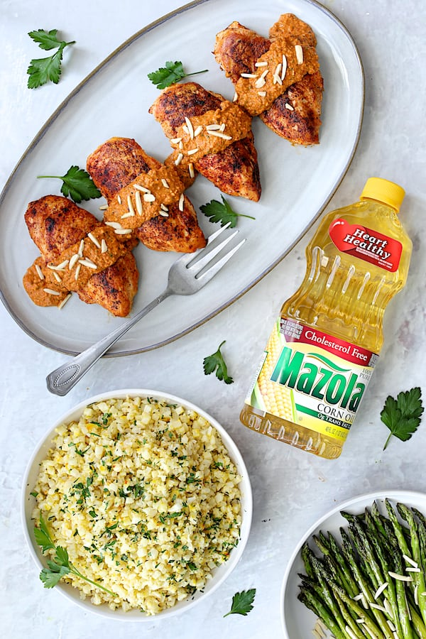 Chicken with Romesco Sauce and Saffron Cauliflower Rice - Overhead shot of dish with bottle of Mazola Corn Oil