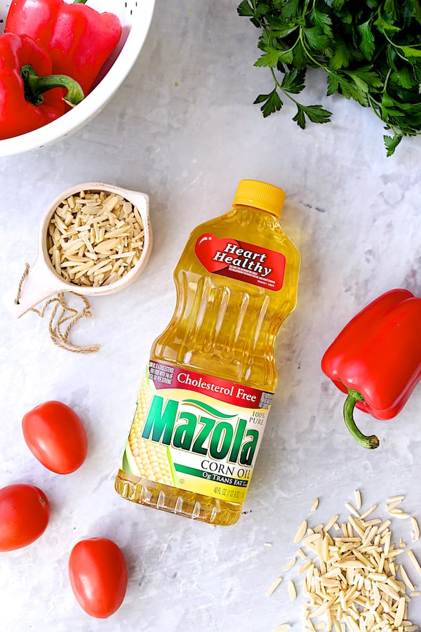 Overhead shot of Mazola Corn Oil bottle with bell peppers, tomatoes, parsley and almonds