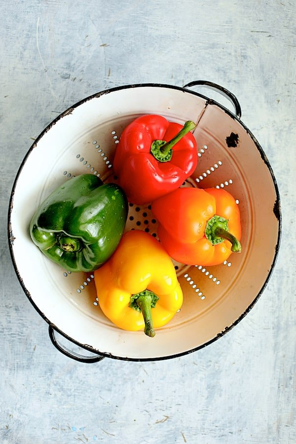 Overhead shot of four colorful peppers in white colander