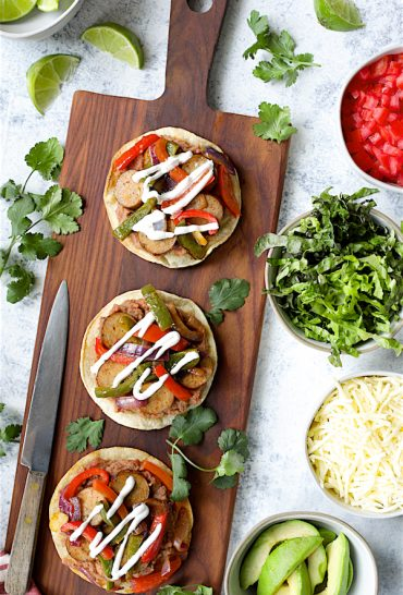 Chicken Sausage Fajita-Style Tostadas - Hero shot of tostadas on wood cutting board with toppings