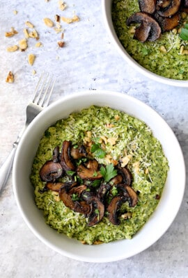 Oven Risotto with Kale Pesto and Roasted Mushrooms - Overhead hero shot of dish in white bowls on pale blue background
