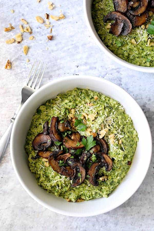 Photo of one serving of Oven Risotto with Kale Pesto and Roasted Mushrooms in white bowl on pale blue background.