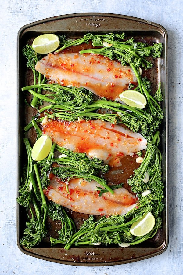 Overhead eshot of fish and broccolini after glazing and before being baked