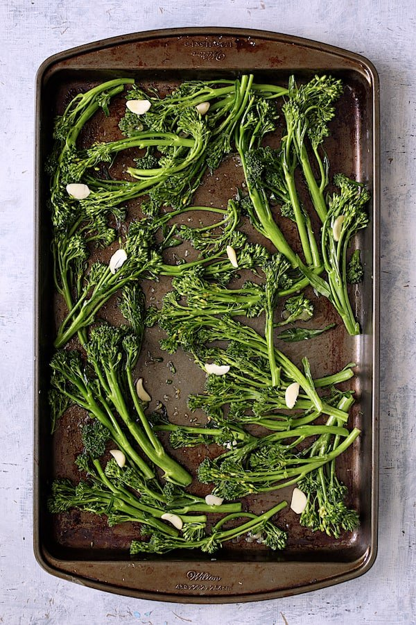 Overhead shot of broccolini with garlic on baking sheet
