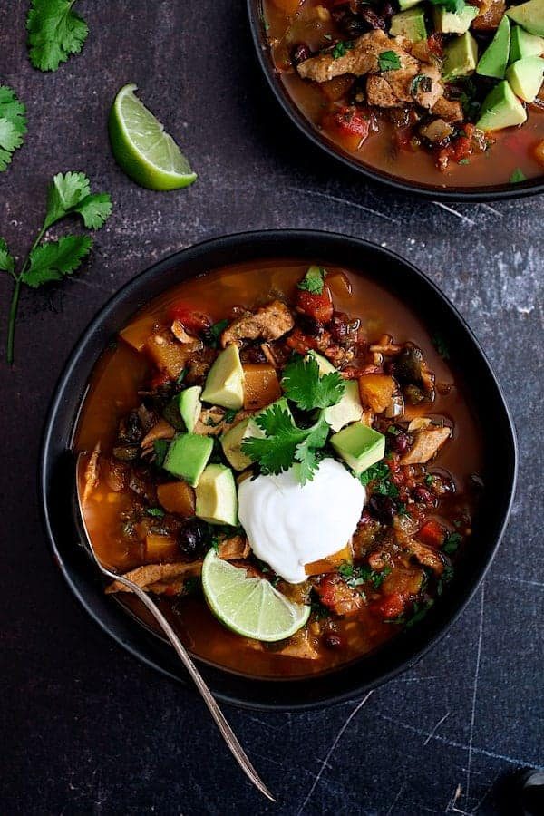 Slow Cooker Southwestern Turkey, Butternut Squash and Black Bean Stew - Overhead hero shot in black bowls garnished with avocado, sour cream and lime