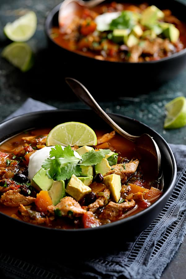 Slow Cooker Southwestern Turkey, Butternut Squash and Black Bean Stew - Straight-on shot of stew in black bowls on dark blue napkin garnished with lime, avocado and sour cream