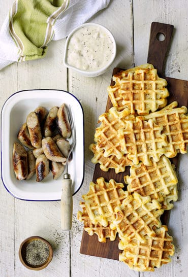 Chicken Sausage and Gravy with Buttermilk - Cheddar Waffles - Overhead hero shot of dish on white distressed wood background