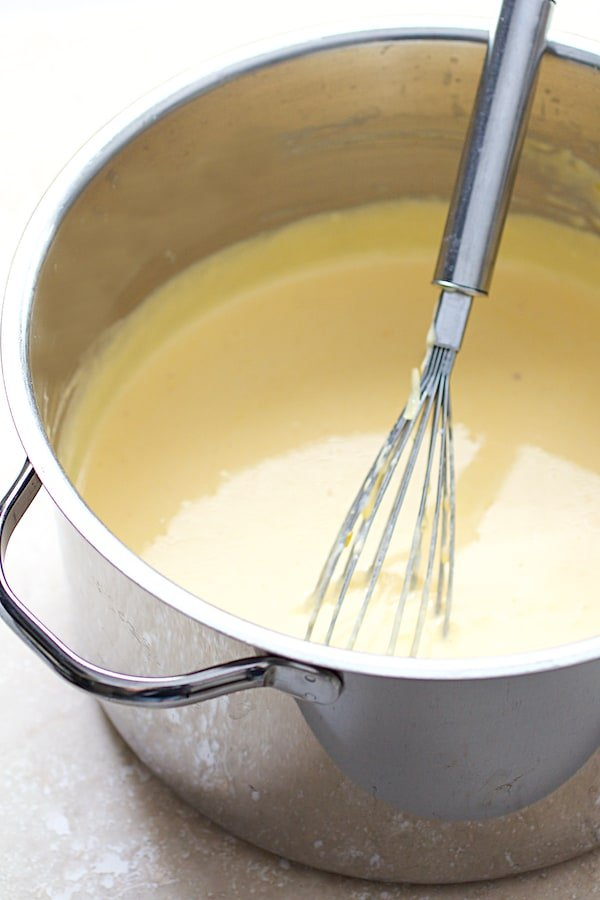Close-up shot of cheese sauce in stainless steel saucepan