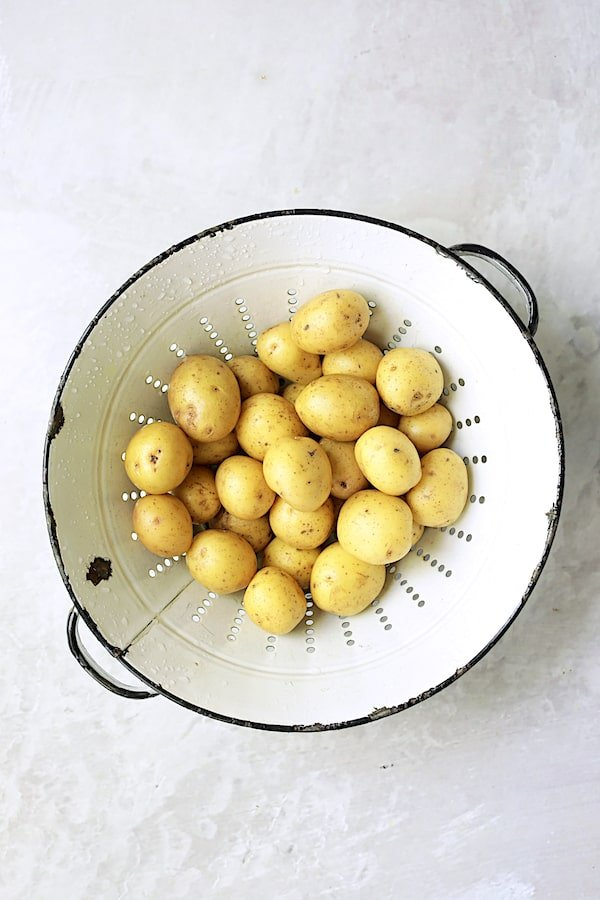 Overhead shot of small Yukon gold potatoes in old white colander