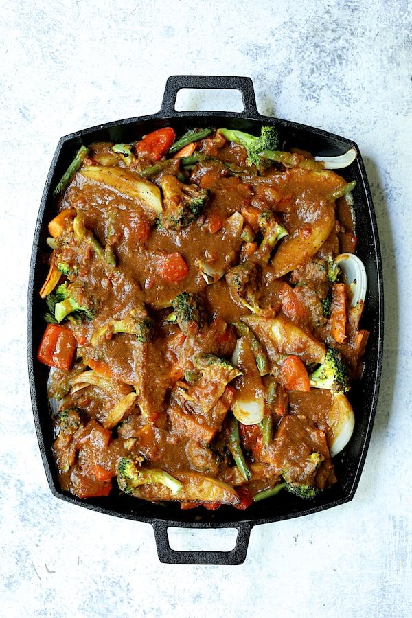 Overhead shot of finished roasted vegetables with sauce added