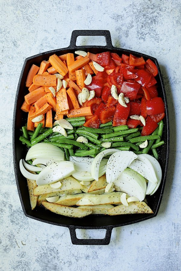 Overhead shot of vegetables on cast iron pan ready for roasting