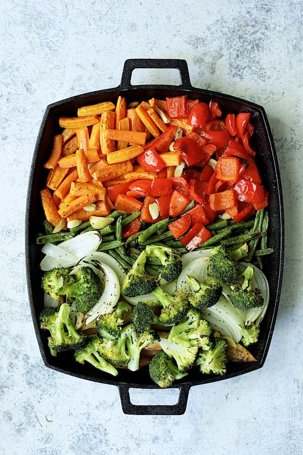 Overhead shot of vegetables on cast iron pan with broccoli added
