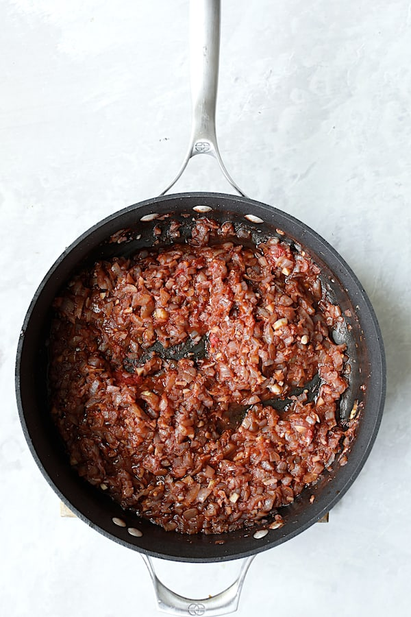 Overhead shot of onions with wine, garlic and tomato paste in skillet