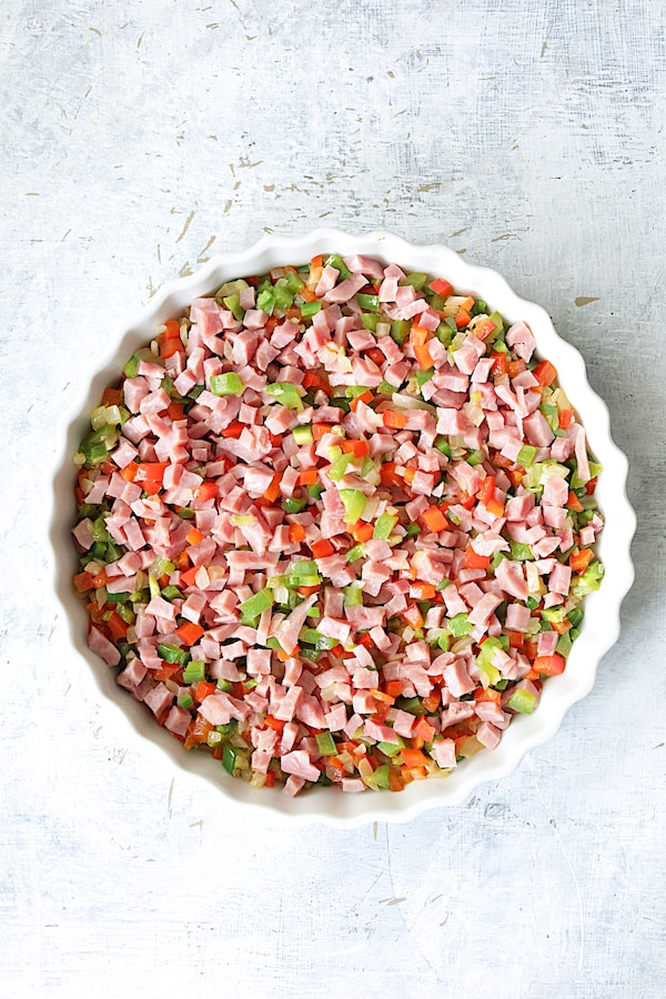 Overhead shot of peppers and ham in round white baking dish