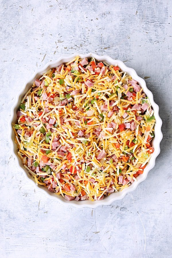 Photo of peppers, ham and cheese in round white baking dish before custard is poured in.