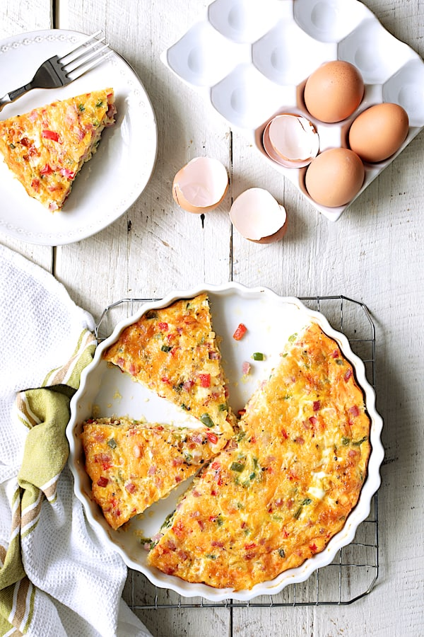 Spicy Baked Denver Omelet - Overhead shot of quiche on white distressed wood background with eggs