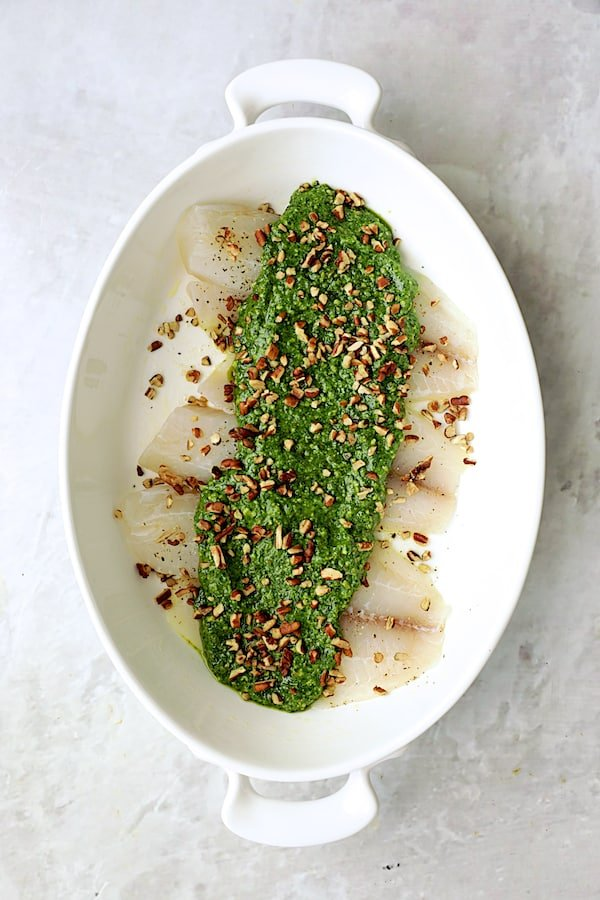 Photo of uncooked tilapia with pesto over the top.