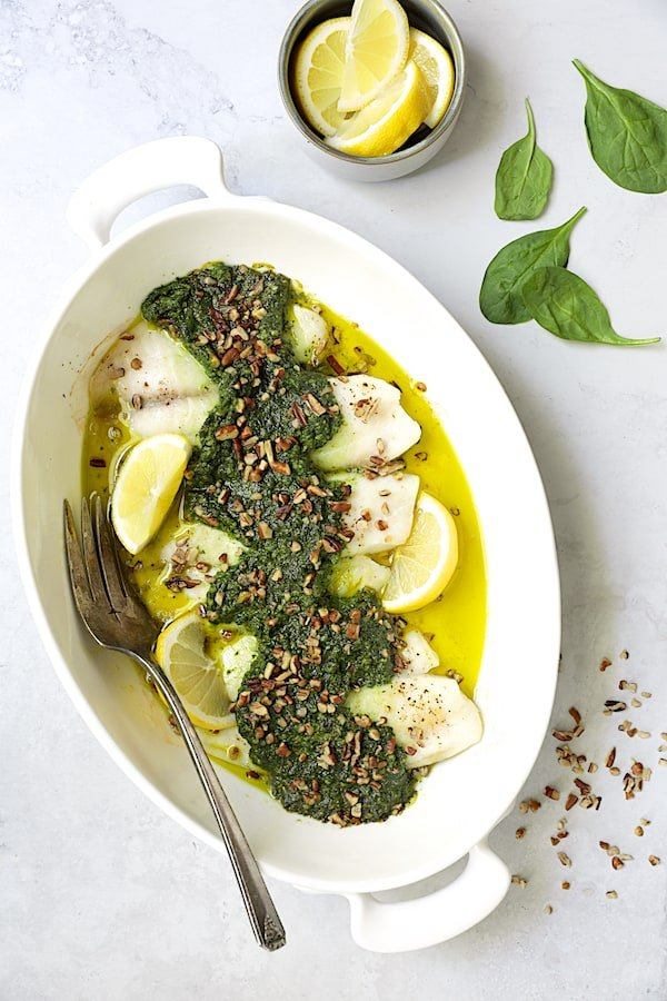 Photo of Baked Tilapia with Spinach Pecan Pesto in white baking dish with serving fork.