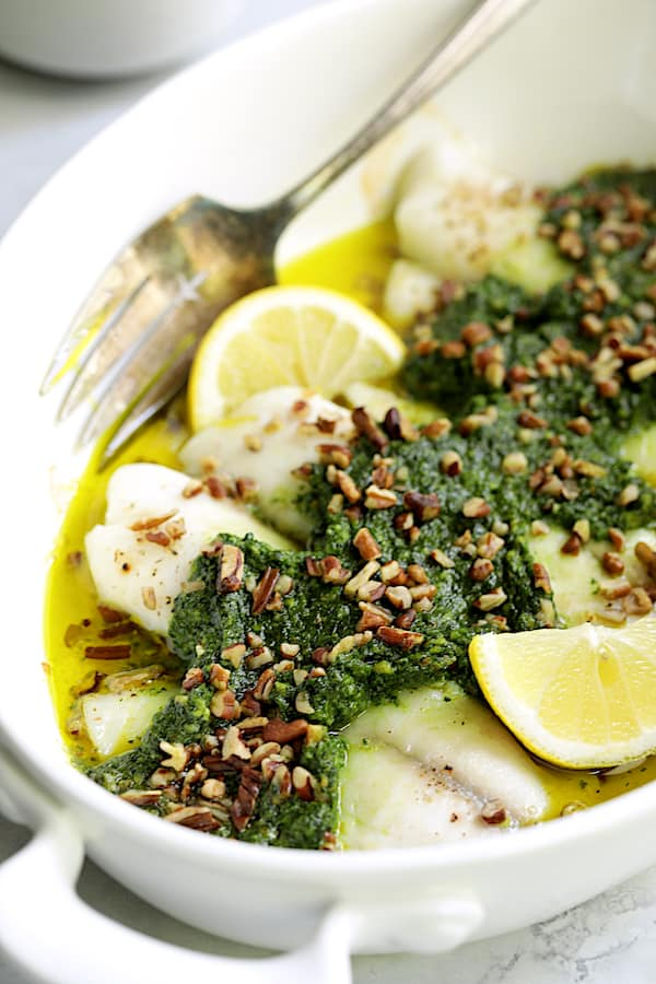 Close-up photo of Baked Tilapia with Spinach Pecan Pesto in white baking dish garnished with chopped pecans and lemon wedges.
