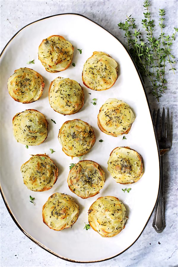 Garlic Herb Muffin Pan Potato Galettes - Overhead shot of galettes on white oval platter garnished with fresh thyme