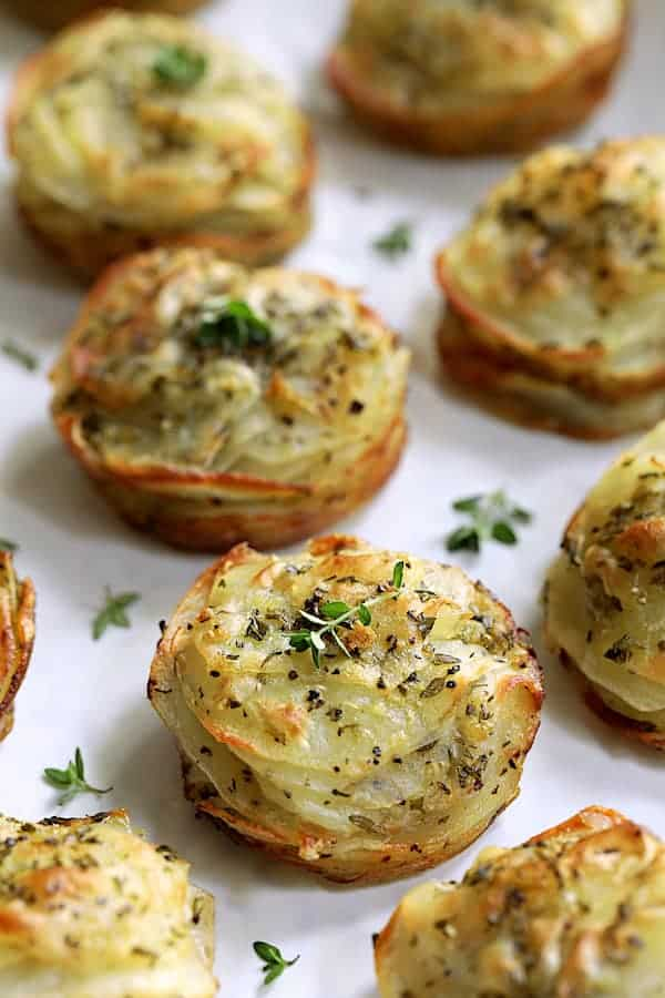 Photo of Garlic Herb Muffin Pan Potato Galettes on white background garnished with fresh thyme.