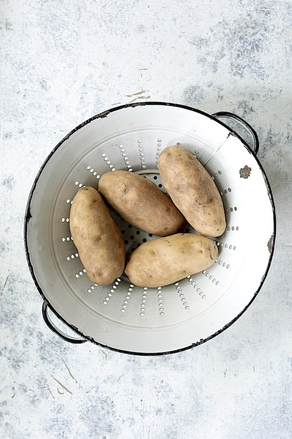 Overhead shot of four Russet potatoes in white antique colander