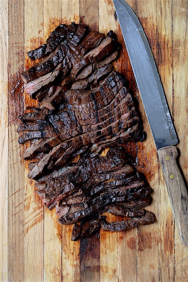 Overhead shot of sliced skirt steak on wood cutting board