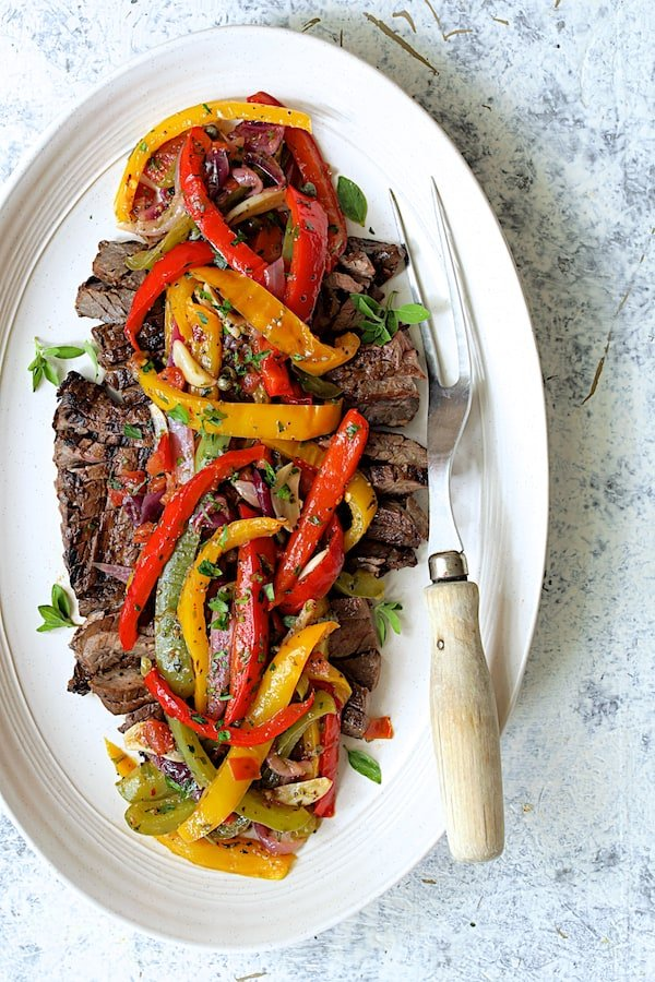 Grilled Marinated Skirt Steak with Peperonata - Overhead shot on pale blue background garnished with fresh oregano