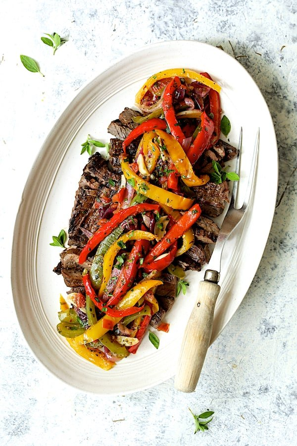 Photo of Grilled Marinated Skirt Steak with Peperonata on white oval platter with meat fork.
