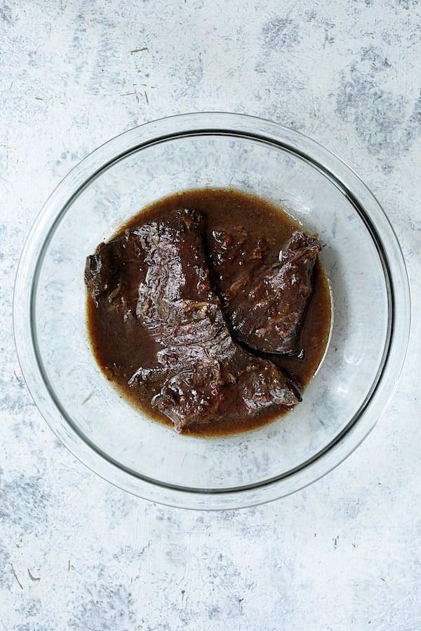 Overhead shot of skirt steak marinating in glass bowl