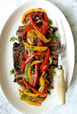 Grilled Marinated Skirt Steak with Peperonata - Overhead hero shot of dish on white oval platter with meat fork