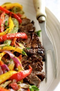 Grilled Marinated Skirt Steak with Peperonata - Straight-on close-up shot of dish on white oval platter