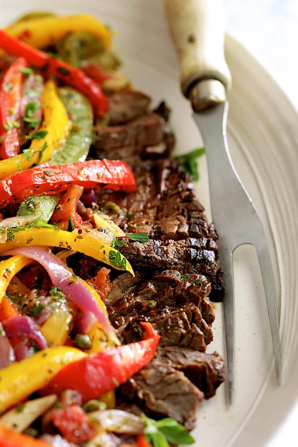 Close-up photo of Grilled Marinated Skirt Steak with Peperonata on white oval platter with meat fork.
