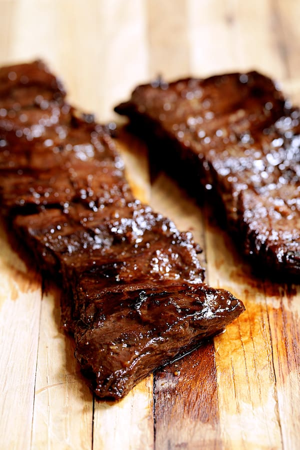 Close-up shot of grilled skirt steak on wood cutting board
