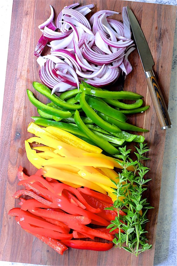Photo of multicolored peppers and onions on wood cutting board.