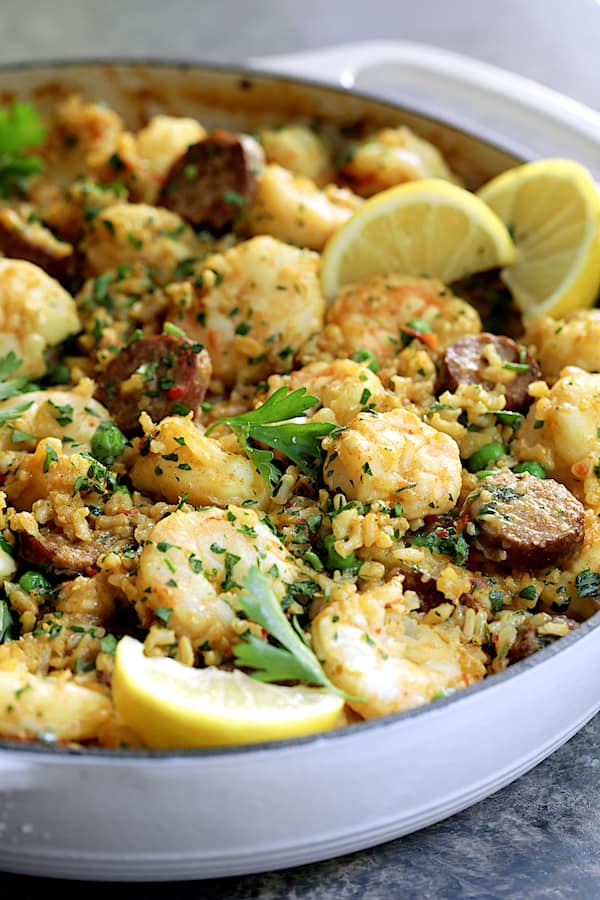 Paella-Style Brown Rice with Shrimp and Chorizo - Straight-on close-up shot of dish in white cast iron pan with lemon and parsley