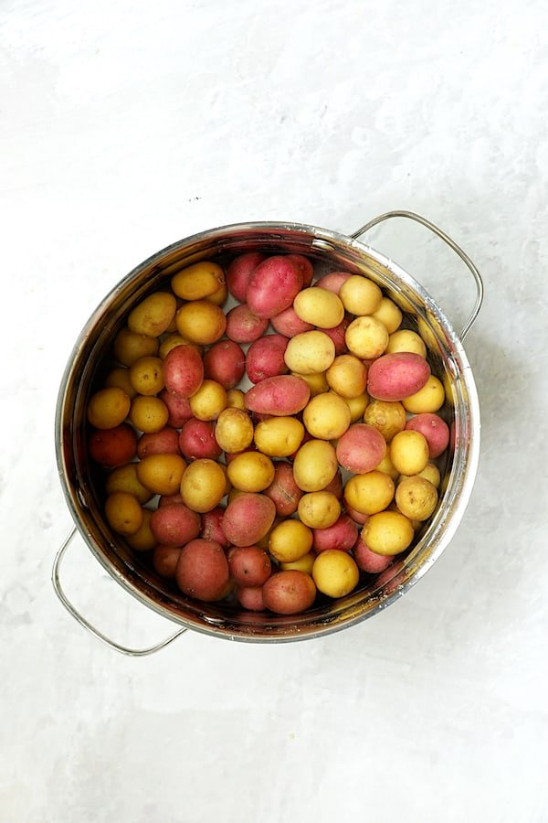Overhead shot of baby red and yellow potatoes in stainless steel pot after being cooked