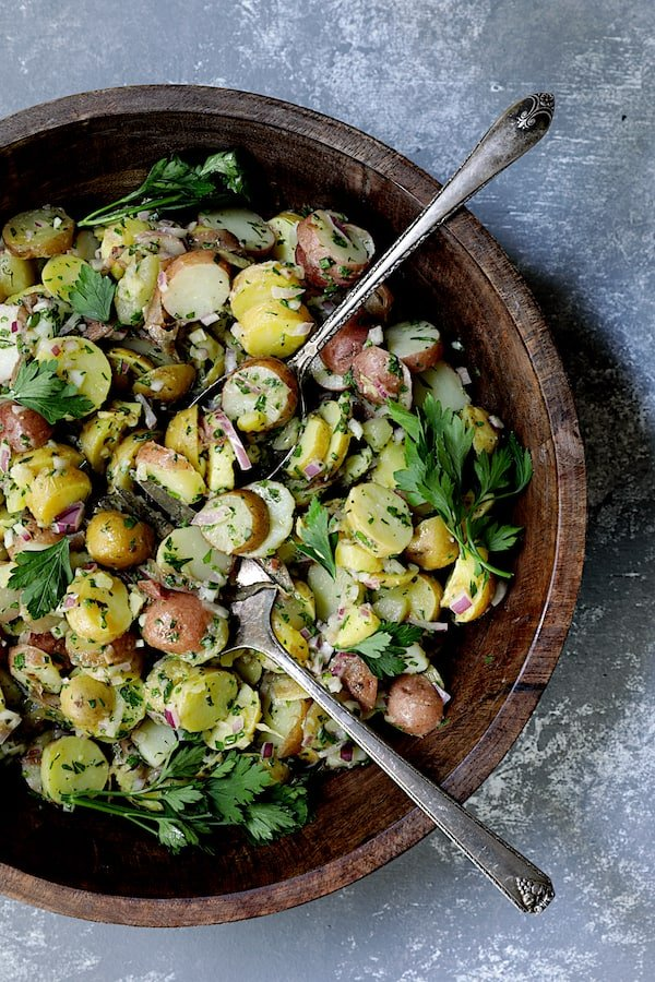 French-Style Potato Salad - Overhead hero shot of salad in wood bowl with serving utensils