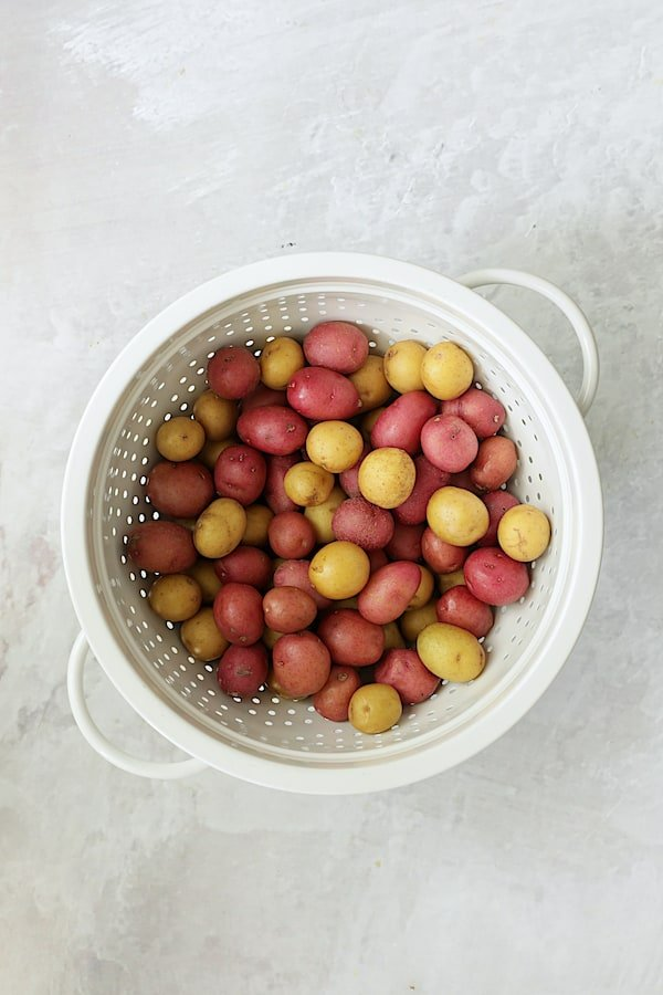 Overhead shot of baby yellow and red potatoes in white colander on white background